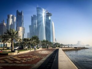 Walking area with some of Qatar's West Bay buildings on the left and on the right the corniche body of water.