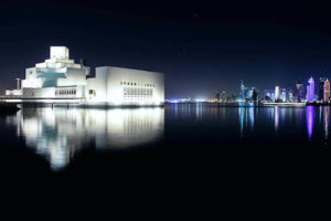The museum building and Qatar skyline in the evening light, with building reflected in the body of water.