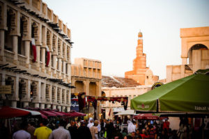 A large crowd of people walking through the souq waqif streets, with restaurants from left and right. There is the finar mosque in the background.