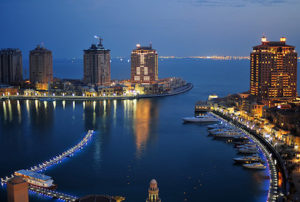 A scenery view of Porto Arabia in the Pearl, with buildings, body of water and boats.