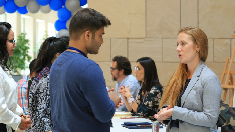 Student speaks to an Academic Services representative at orientation.