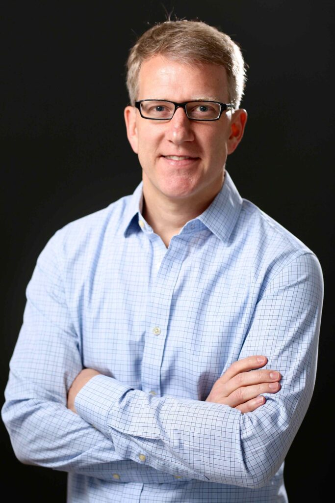 Image of the speaker Sebastian Abbot in a light blue shirt, with his arms crossed and wearing black, rectangular glasses.