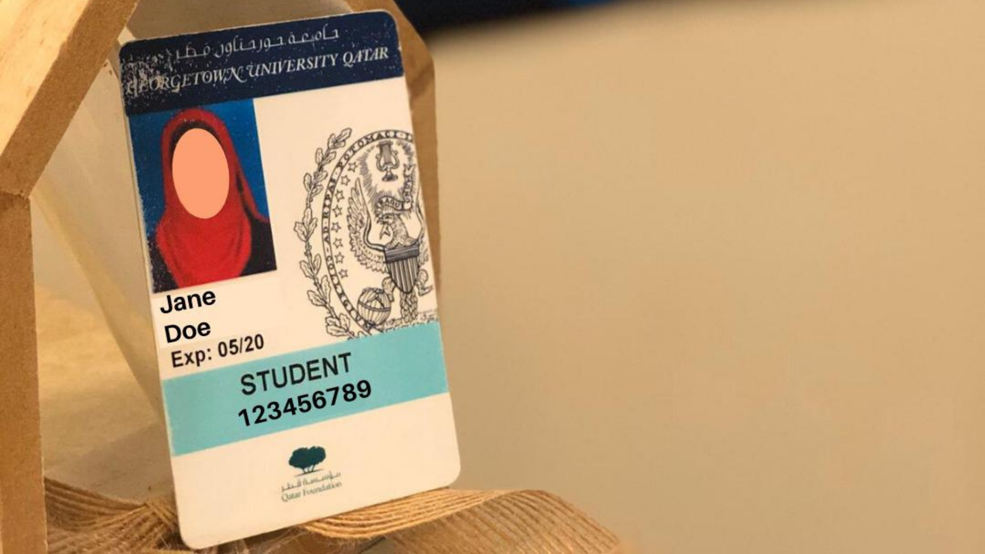 "Picture of a student ID card, with the name ""Jane Doe"" and ID number 12345678, angled on a wooden pentagonal block. There is a blurred Georgetown Poster in the background."