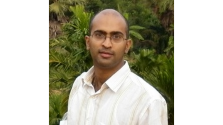 Picture of Jason in a white collared shirt, wearing glasses and looking at the camera, in front of a green plant wall